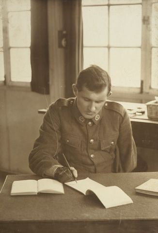 WWI soldier Allan McMillan writing at a desk at Oatlands Park, Surrey, England