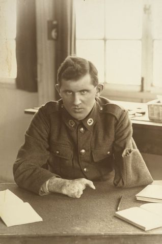 WWI soldier Allan McMillan sitting at a desk at Oatlands Park, Surrey, England