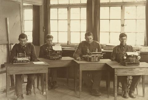 Untitled [Alan McMillan and three other WWI soldiers seated at typewriters at Oatlands Park, Surrey, England], 1918, England, maker unknown. Te Papa (O.031489)