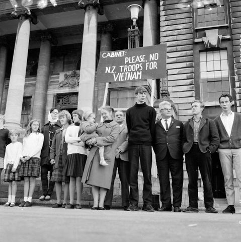 Demonstrators on Parliament steps, Wellington, protest against New Zealand sending combat troops to Vietnam. A banner behind them reads: 'Cabinet: Please, no N.Z. troops for Vietnam'