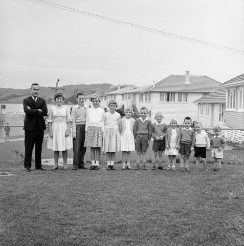 Peter Parker and his 11 children at their state house, Te Pene Avenue, Titahi Bay, Porirua, New Zealand, Left to right: Peter, Julie (14), Bernard (13), Christine (11), Angela (10), Brenda (9), Timothy (7), Stephen (6), twins Helen and Lawrence (5), Michael (4), Nicholas (2)