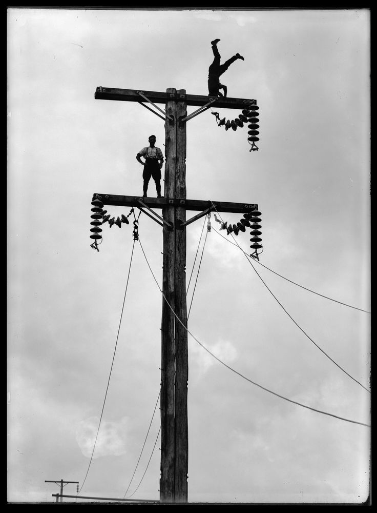 Leslie Adkin. C. Cusack (top) and mate on a Queen St, Levin transmission pole, part of the Mangahao-Wellington transmission line, 14 December 1923. Gelatin silver print. Te Papa (B.023155)