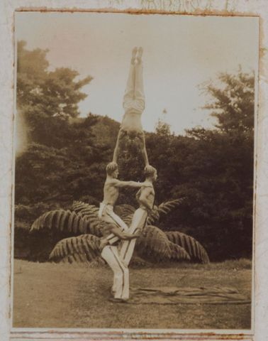 [four men in acrobatic pose in front of fern]