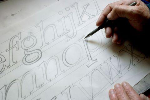 Detail of Joseph Churchward sketching at his desk. Photograph by Norman Heke, Te Papa, 2008