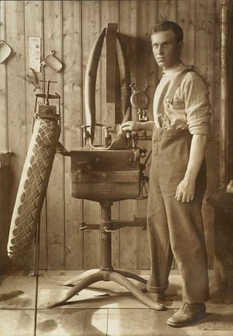 Unidentified WWI soldier with an amputated foot mending a car tyre, England, 1918, maker unknown. Acquisition history unknown. Te Papa (O.031466)