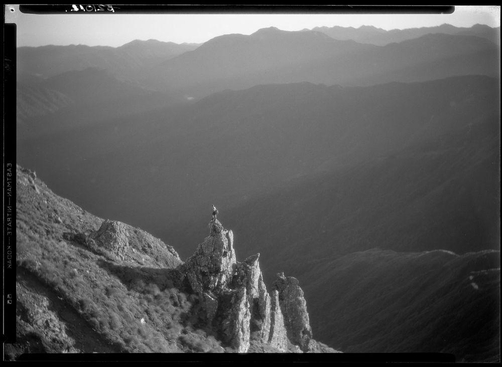 Leslie Adkin. Early morning sunbeams over the Otaki valley. View towards Mt Crawford from West Peak. J.K. Nichols on pinnacle, 29-30 March 1930. Gelatin silver print. Te Papa (B.021011)