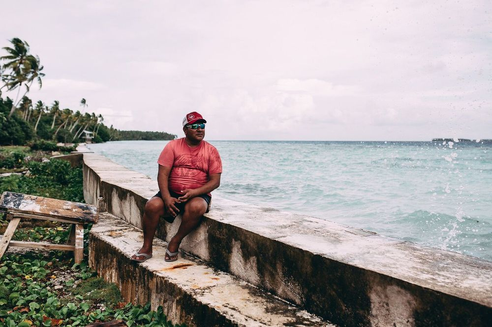 Co-collector Atonio Tuia sitting on sea wall next to the submerged field where he played rugby as a youth, Nukunonu, Tokelau