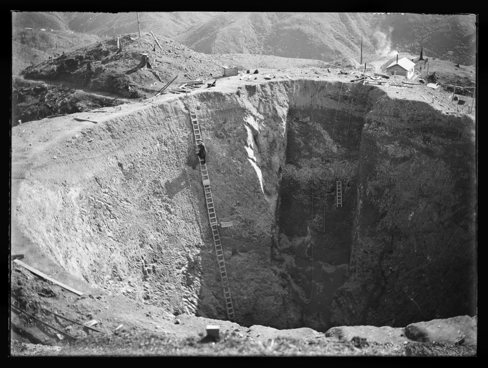 Leslie Adkin. The excavation for the surge chamber completed and ready for the lining of concrete. The pit is 75ft. in diameter at the top and 75ft. deep, 27 August 1922. Gelatin glass negative. Te Papa (B.022963)