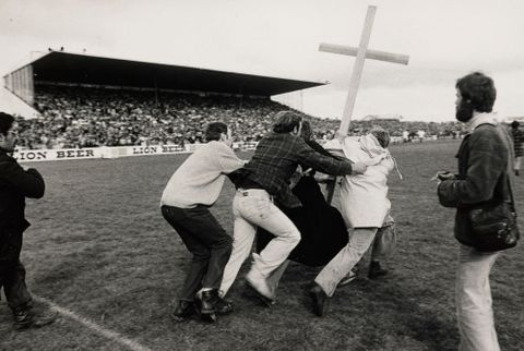 O.003025; Two members of St John's College run onto Rugby Park, Hamilton, while two supporters of Springbok Rugby Tour try to stop them, 1981;1981; Black, Peter; cropped (image/jpeg)
